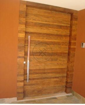 Porta de entrada pivotante feita toda em madeira de demolição